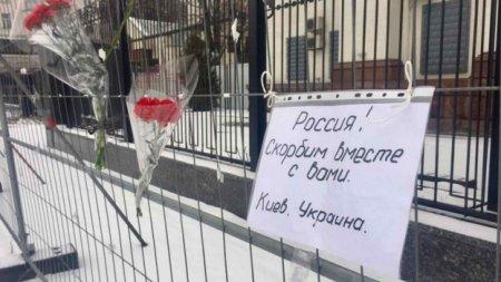 Украинцы несут цветы и свечи к зданию посольства России в Киеве